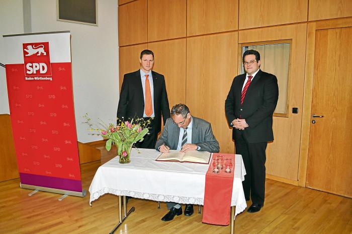 Innenminister Reinhold Gall trägt sich ins goldene Buch von Frickenhausen ein. V.l.n.r. Sven Rahlfs (Ortsvereinsvorsitzender), Reinhold Gall (Innenminister BW, MdL), Simon Blessing (Bürgermeister).